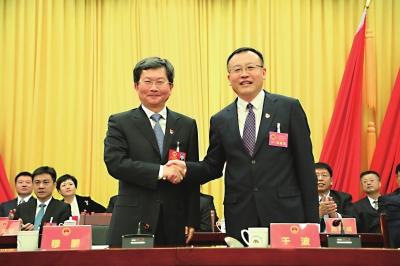穆鹏同志(左)与新当选的北京市延庆区区长于波同志(右)亲切握手